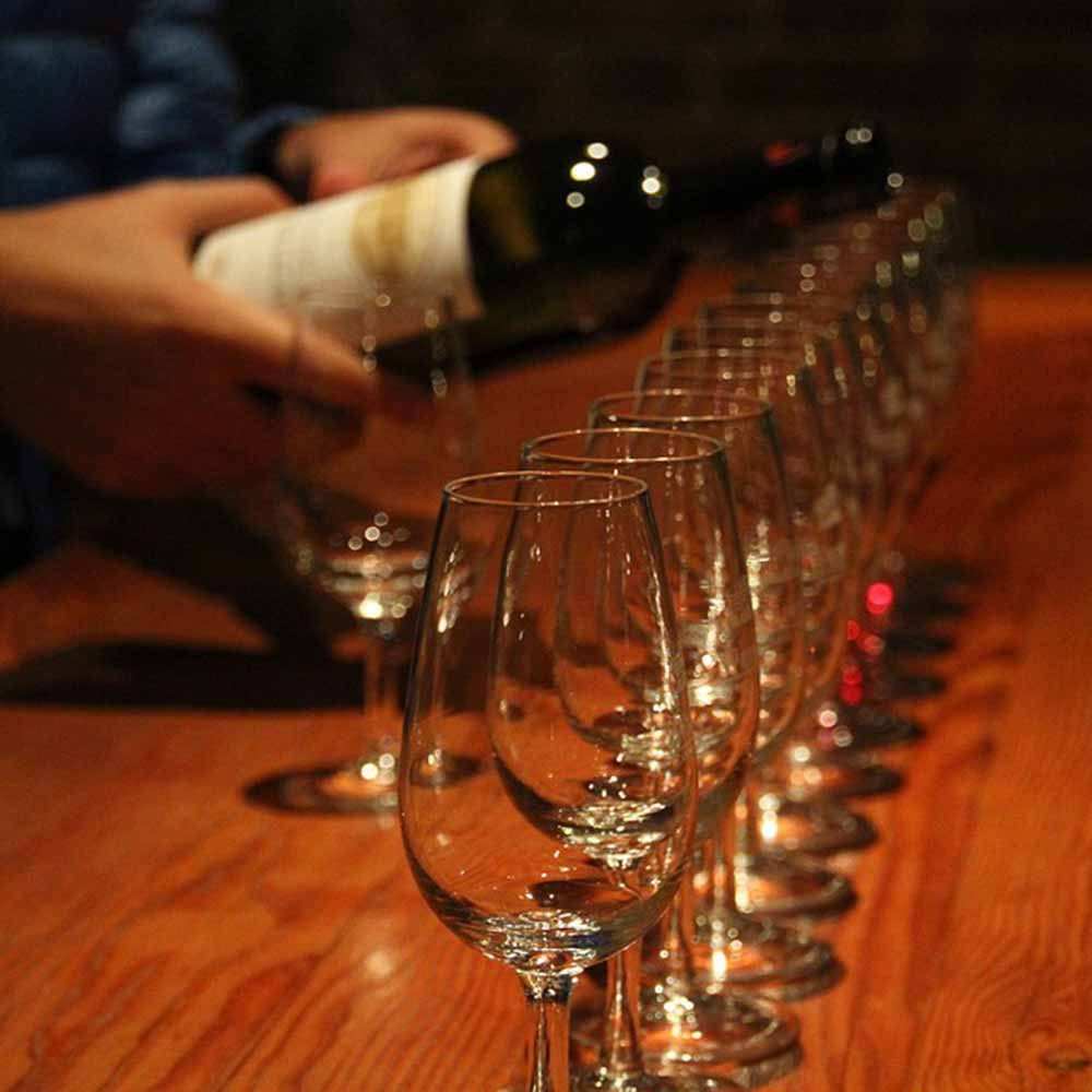 pouring wine into a flight of glasses
